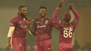 West Indies captain Kieron Pollard (left) celebrates a wicket with pace bowler Romario Shepherd and Hayden Walsh Jr during their first ODI against Afghanistan in  Lucknow, India.
