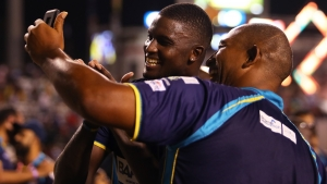 Barbados Tridents skipper Jason Holder (left) and coach Phil Simmons celebrate after their team claimed the Hero Caribbean Premier League title on Saturday.