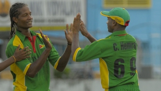 Guyana's Clinton Pestano is congratulated by teammate Chandrapaul Hemraj.